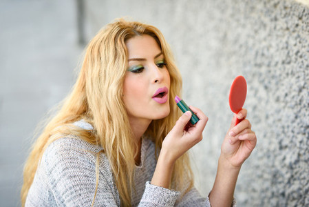 Young blonde woman applying lipstick looking at mirror in the st