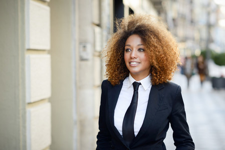 Black businesswoman wearing suit and tie in urban background