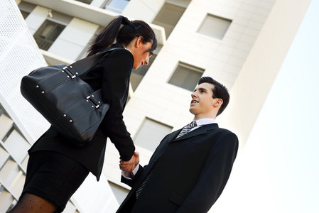 Businessman and businesswoman shaking hands outside of office bu