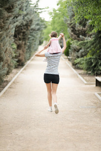 Little girl walking on the shoulders of her mother