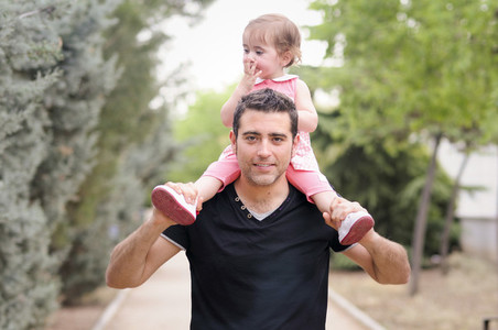 Little girl walking on the shoulders of her father