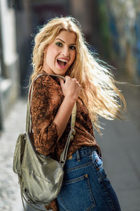 Pretty blond woman  model of fashion  smiling with flying hair