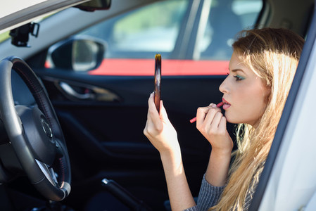 Blonde woman applying lipstick looking at mirror in her car
