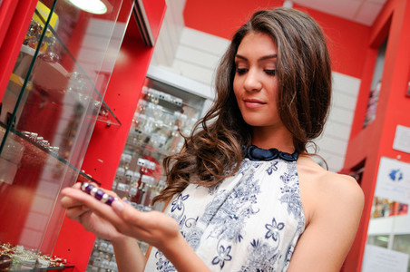 Attractive young woman buying a bracelet at a jewelry