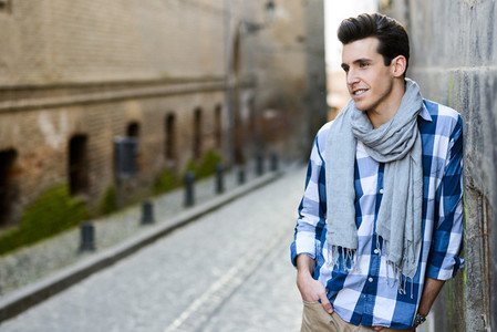 Handsome man with modern hairstyle smiling in urban background
