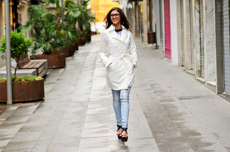 Beautiful woman with eyesglasses walking in urban background