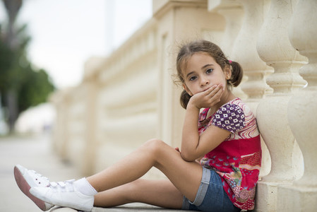 Adorable little girl combed with pigtails sitting on floor