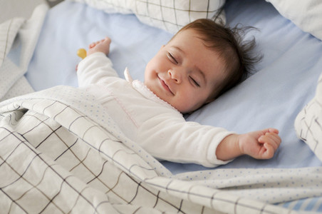 Smiling baby girl lying on a bed