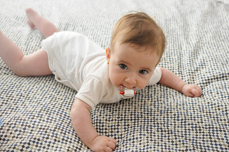 Baby girl four months old on the bed with pacifier
