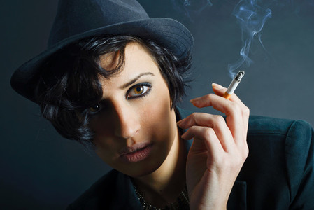 Brunette woman smoking a cigarette on black background wearing a