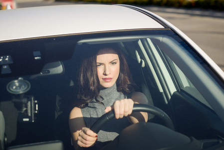 Brunette woman driving a white car in urban background
