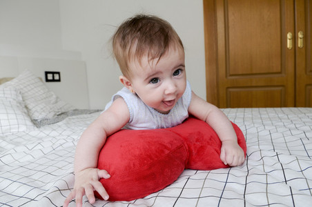 Baby girl four months old on the bed