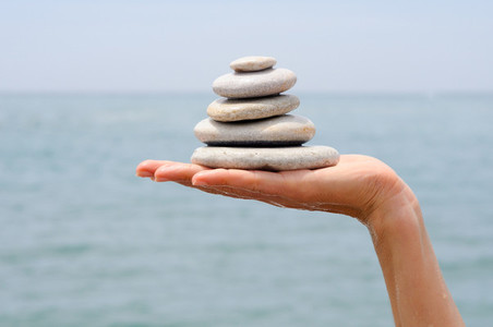 Gravel pile in womans hands with sea background