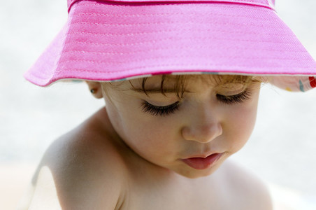Close up potrait of adorable little girl wearing sun hat