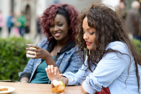 Portrait of two women taking a drink in a bar  Urban background