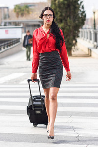 Hispanic stewardess crossing street with luggage bags