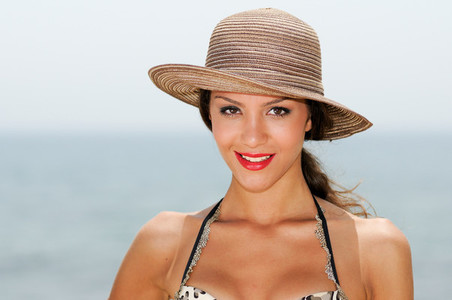 Woman with beautiful hat on a tropical beach