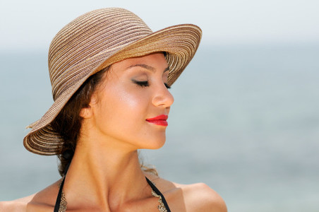Attractive woman with a sun hat on a tropical beach eyes closed