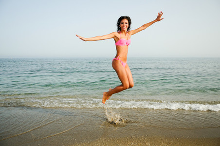Woman with beautiful body jumping in a tropical beach