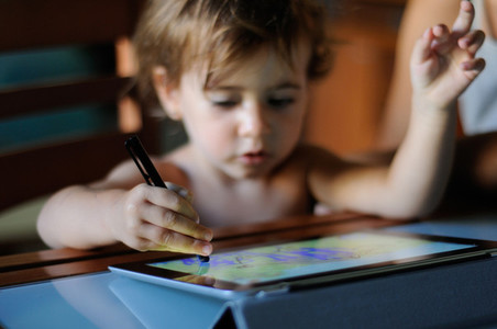 Little girl painting with a digital tablet at home