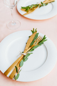 Festive table setting for celebrate event or family dinner with two plates and golden cutlery on a pink tablecloth