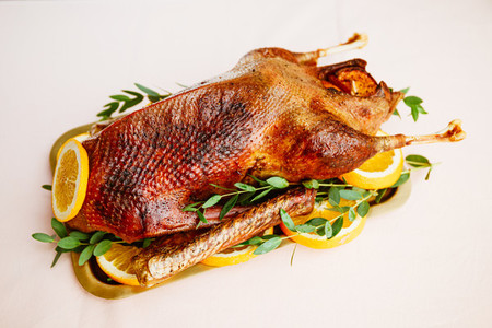 Roasted goose with oranges on a golden tray for celebrate event Thanksgiving or Christmas family dinner