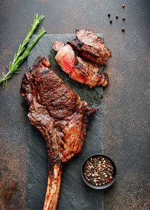 Top view of grilled beef steak Tomahawk with spices on a black slate Flat lay dinner concept