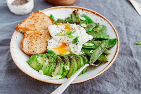 Healthy breakfast or lunch Fried snow peas avocado poached eggs are sprinkled chia seeds with bread toasts