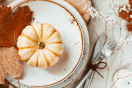 Top view of small pumpkins in a plate decorated Autumn ornate  The concept of Thanksgiving or Halloween