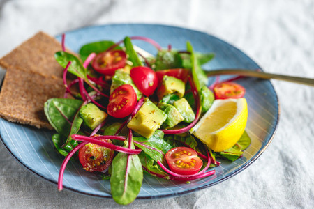Vegetarian healthy salad is made from swiss chard leaves cherry tomatoes avocado lemon juice and olive oil into a ceramic portion plate