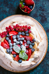 New Zealand Pavlova cake with whipped cream and mix of fresh berries on a blue textured background