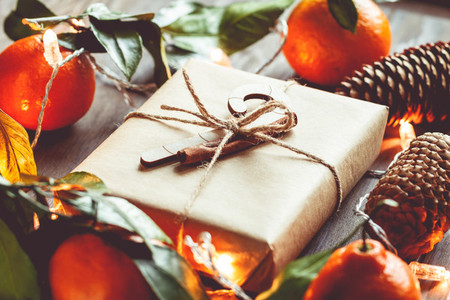 Christmas gift box in a kraft paper among tangerines and fir cones on a festive table The concept of cosy winter Holidays