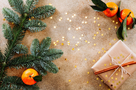 Fir branch tangerines and Christmas gift box on a beige textured background with gold stars confetti Flat lay top view copy space