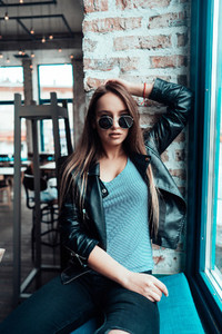 Beautiful girl in sunglasses posing on camera