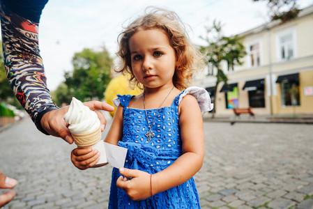 Beautiful little girl holds ice cream