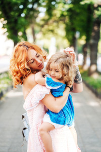 Woman hugs her daughter holding her in her arms