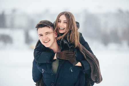 man carries his girlfriend on the back