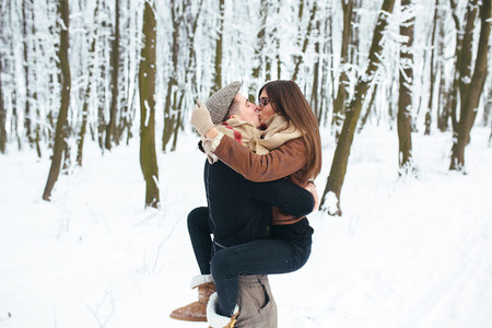 guy holds the girl on hands in snow park