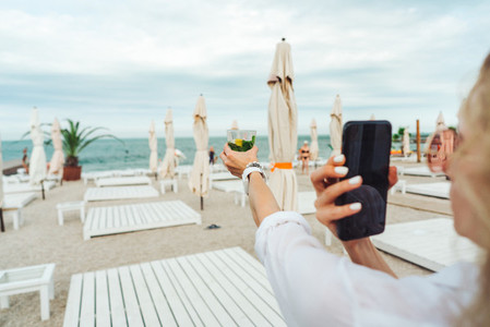 holding a phone and taking a picture of a cocktail