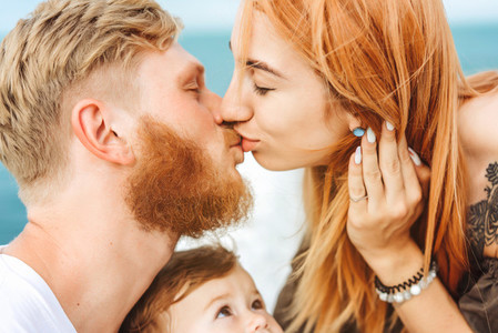 Mom and Dad kiss  Happy family on vacation