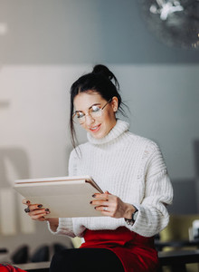 Brunette woman with eyeglasses using tablet