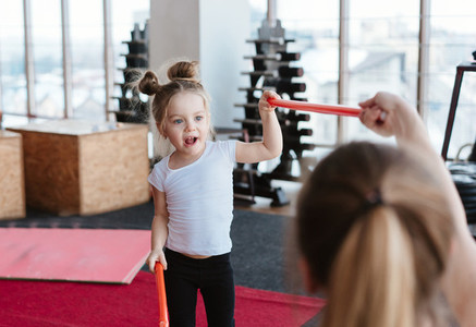 Little girl and mom doing exercises with sticks