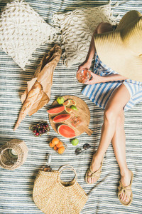 Picnic concept with woman in dress wine fruits and baguette