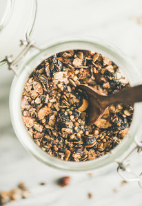 Buckwheat and granola with hazelnuts in glass jar with spoon