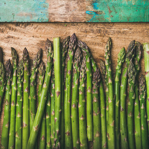 Raw green asparagus in row over rustic background  square crop