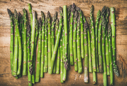 Raw uncooked green asparagus in row over wooden background
