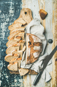 Flat lay of sourdough wheat bread cut in slices on board