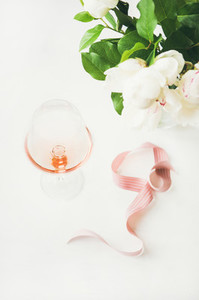 Rose wine in glass  pink decorative ribbon  peony flowers