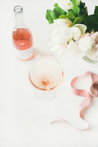 Rose wine in glass  pink ribbon  peony flowers  copy space