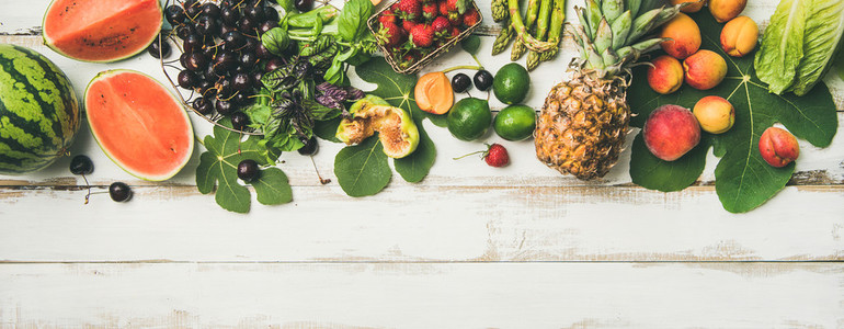 Seasonal fruit vegetables and greens over wooden background wide composition